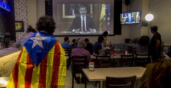 Varias personas miran el discurso del rey Felipe VI en un bar en Barcelona, al final de la jornada de paro general en protesta por la actuación policial durante el referéndum del 1-O. EFE/Quique García