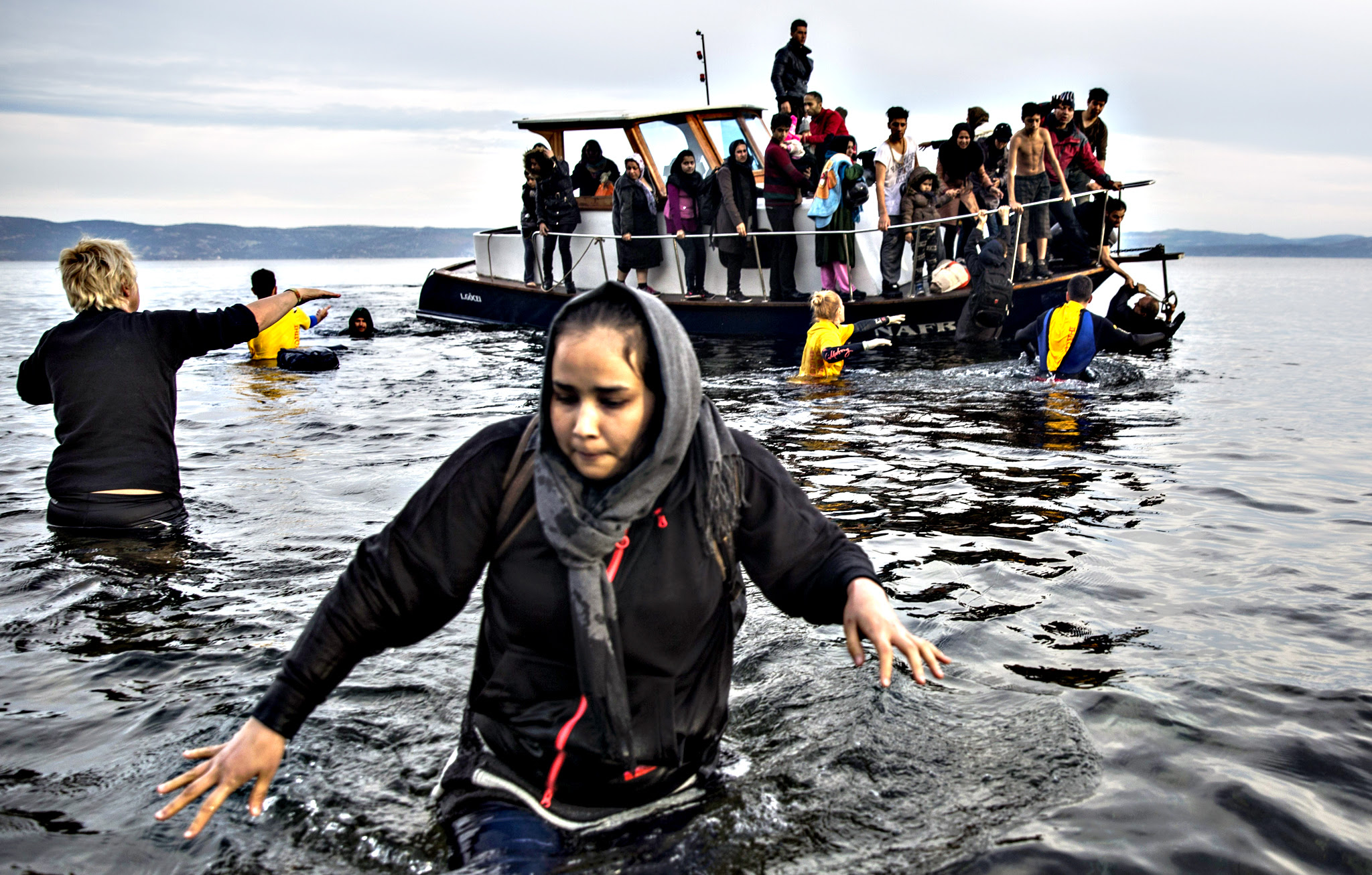 A girl walks through the water as other migrants and refugees helped by volunteers  to disembark from a small boat after their arrival from the Turkish coast on the northeastern Greek island of Lesbos  Monday, Nov. 16, 2015. Greek authorities say 1,244 refugees and economic migrants have been rescued from frail craft in danger over the past three days in the Aegean Sea, as thousands continue to arrive on the Greek islands