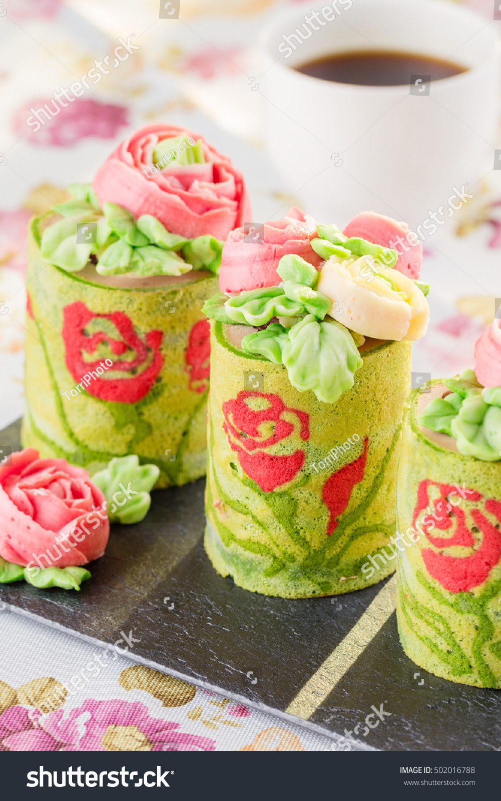 http://www.shutterstock.com/pic-502016788/stock-photo-spring-green-roll-cake-pastries-decorated-with-buttercream-flowers-modern-european-desserts-shallow-focus.html