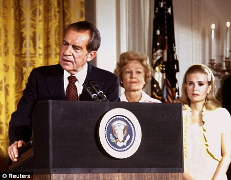 Family man: President Richard Nixon, left, gives a speech as he is listened to by First lady Pat Nixon, centre, and daughter Tricia Nixon, right