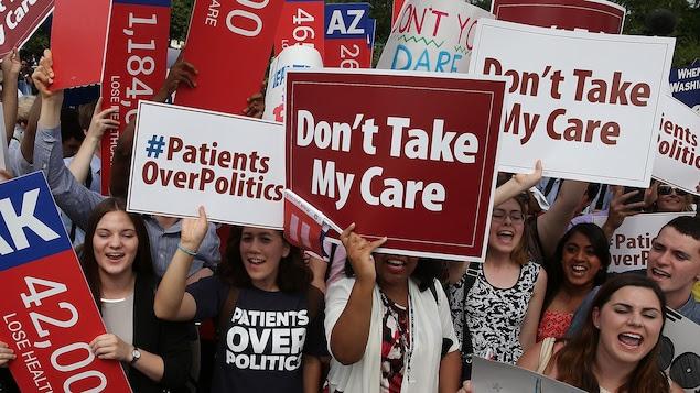 Des jeunes tiennent des pancartes où il est écrit : « Ne prenez pas mes soins de santé ».