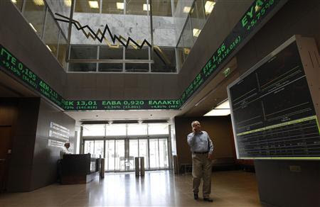 A man walks next to an electronic board at the reception hall of the Athens stock exchange June 19, 2012. REUTERS/John Kolesidis
