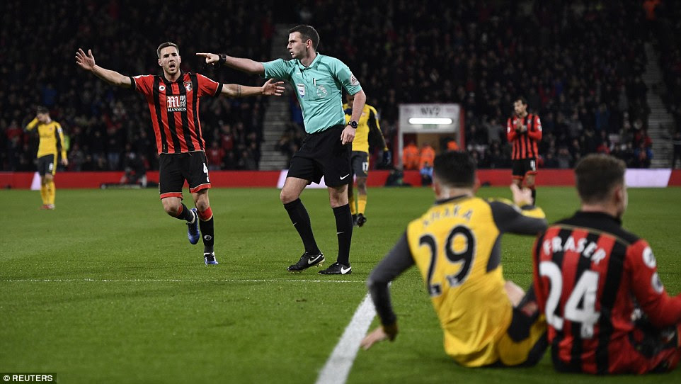 Referee Michael Oliver pictured pointing towards the penalty spot after the foul by Xhaka on Fraser