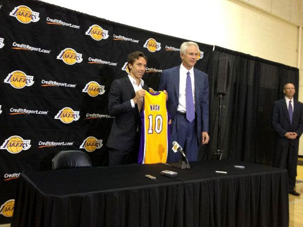 With Lakers General Manager Mitch Kupchak standing nearby, Steve Nash presents the jersey that he's going to wear for the next 3 NBA seasons.