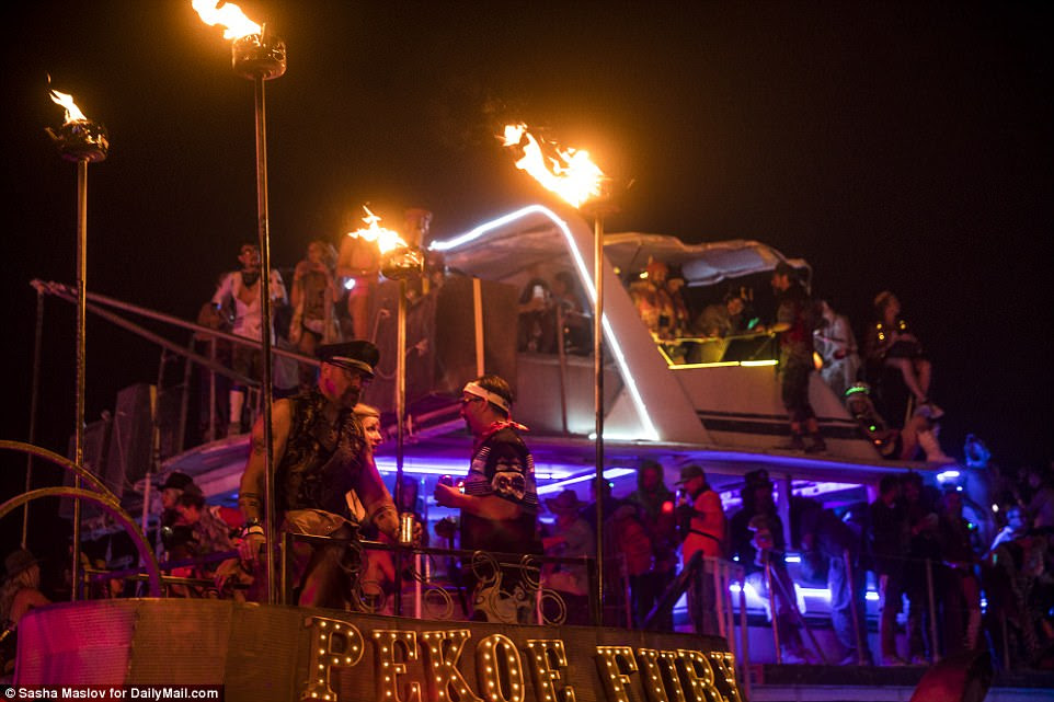 Leather clad men dressed as police officers and sailors locked in discussion underneath burning torches and neon lights