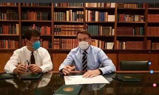 Com máscaras no rosto, Bolsonaro faz transmissão ao vivo com ministro da Saúde Foto: Reprodução