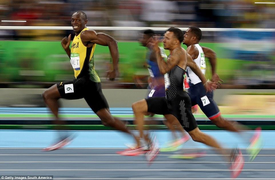 É muito fácil para Usain Bolt, que tem tempo para sorrir durante sua 100m semi-final no caminho para um sprint 'Triplo'