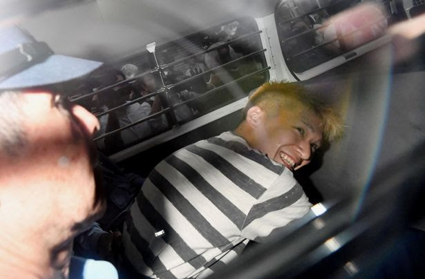 Satoshi Uematsu, suspected of a deadly attack at a facility for the disabled, is seen inside a police car as he is taken to prosecutors, at Tsukui police station in Sagamihara, Kanagawa prefecture, Japan