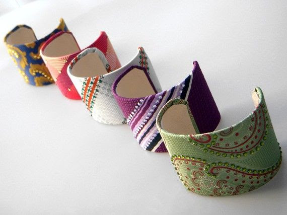 up-cycled neck ties on aluminum adjustable cuffs. Embellished w/ Swarovski crystals.