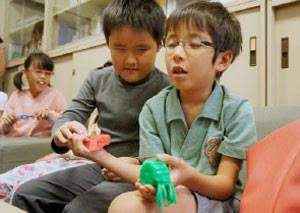 Crianças japonesas cegas manuseiam objetos feitos com impressora 3D do Yahoo. (Foto: Divulgação/Yahoo)
