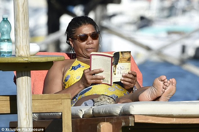 Book worm: The 44-year-old enjoyed a spot of reading with the novel The Queen Of Harlem, by Brian Keith Jackson