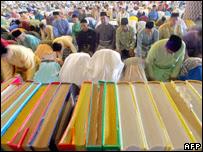Malaysian Muslims pray behind of the Koran during a special morning prayer at the National Mosque in Kuala Lumpur