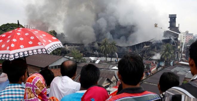 Varias personas miran las labores de extinción del incendio en Daca. REUTERS/Mohammad Ponir Hossain