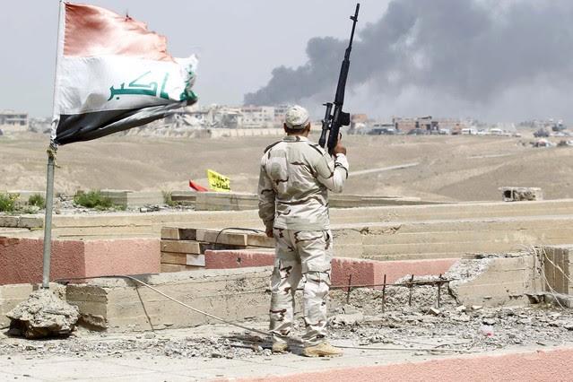 Un miembro de las tropas iraquís observa el combate contra Estado Islámico en Tikrit.