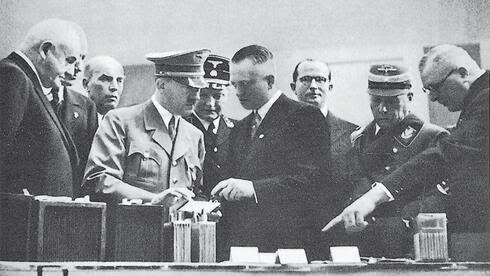 Hitler lässt sich 1938 auf dem Messestand der AFA die neuesten technischen Entwicklungen zeigen. Auf dem Foto ist Günther Quandt links abgebildet, rechts neben Hitler steht Edgar Haverbeck, im Hintergrund (mit Brille) Quandts Sohn Herbert. Quelle: Verlag C.H Beck