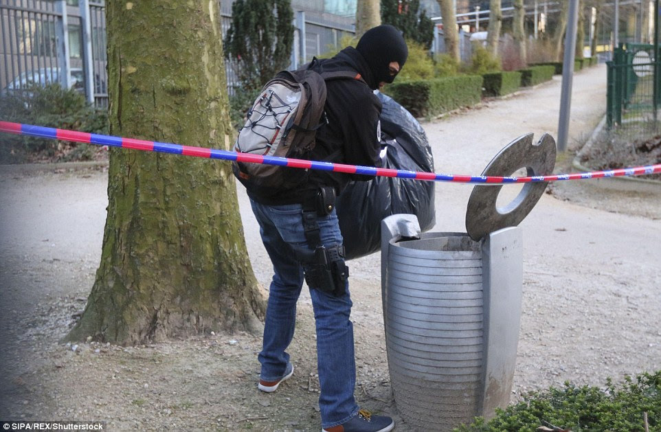 Collecting evidence? Police search for evidence and empty a public bin near the Maelbeek metro station which was bombed earlier today