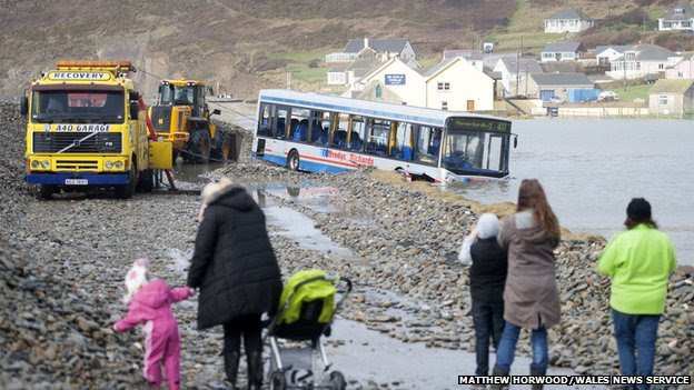 Council workers clear the road so that the stranded bus can be moved