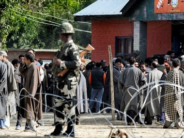 Security personnel keep vigil as voters line up outside a polling booth in Jammu and kashmir's Bandipora on Thursday. PTI