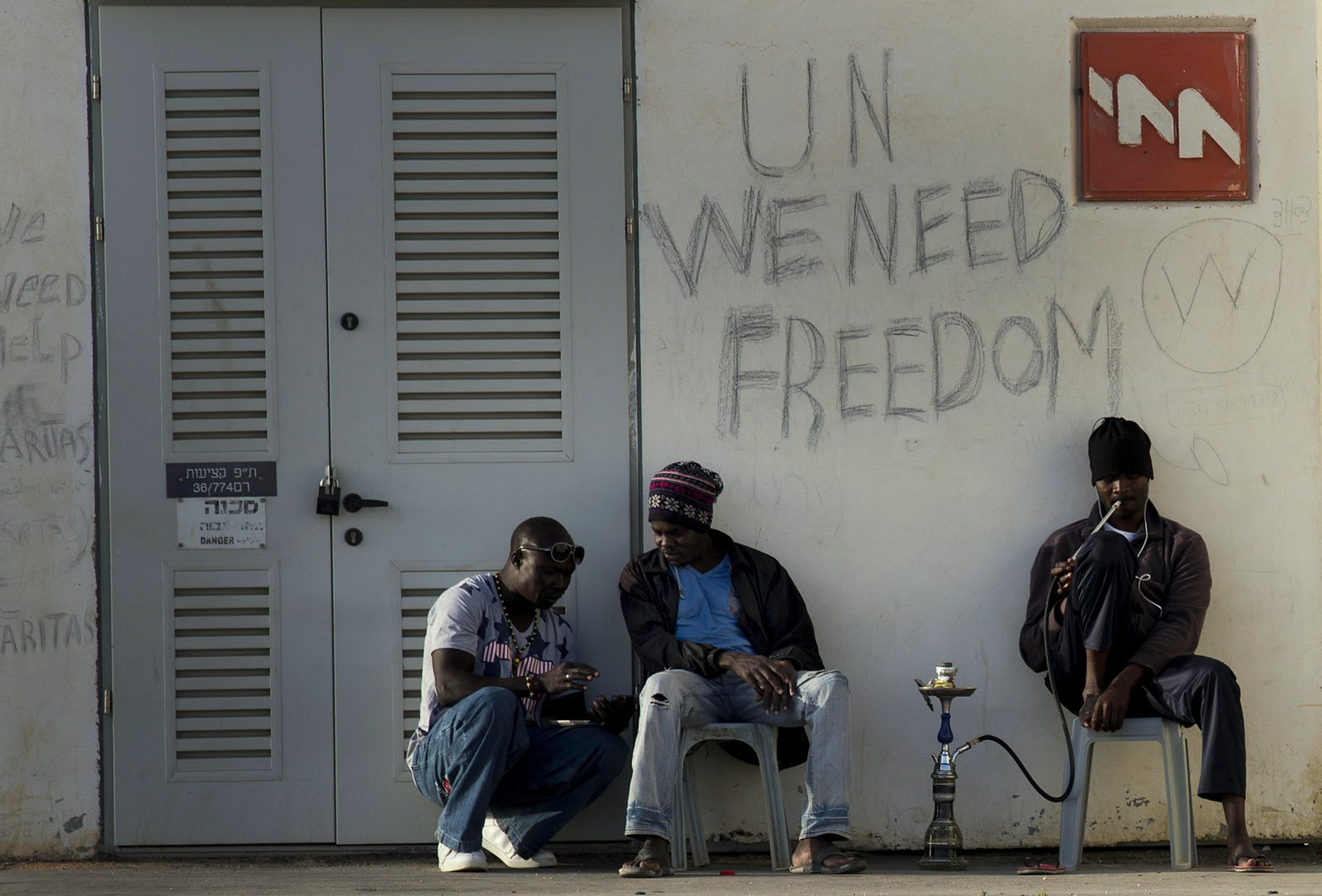African migrants sit outside Holot detention center in the Negev Desert, southern Israel, Tuesday, April 21, 2015. Tens of thousands of African asylum seekers have made their way to Israel in recent years. Most of them came from Eritrea, an eastern African nation with one of the world's most dismal human rights records. (AP Photo/Tsafrir Abayov)