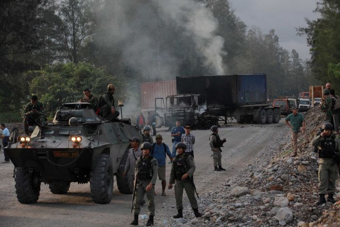 Police and security forces are seen near burning vehicles.