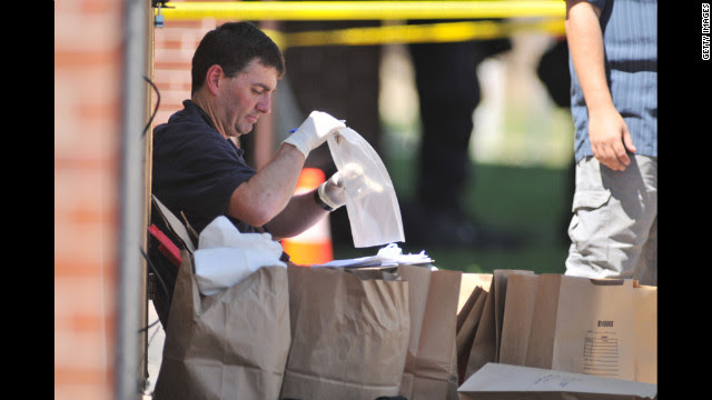 Investigators work on evidence near the apartment of James Holmes on Friday.