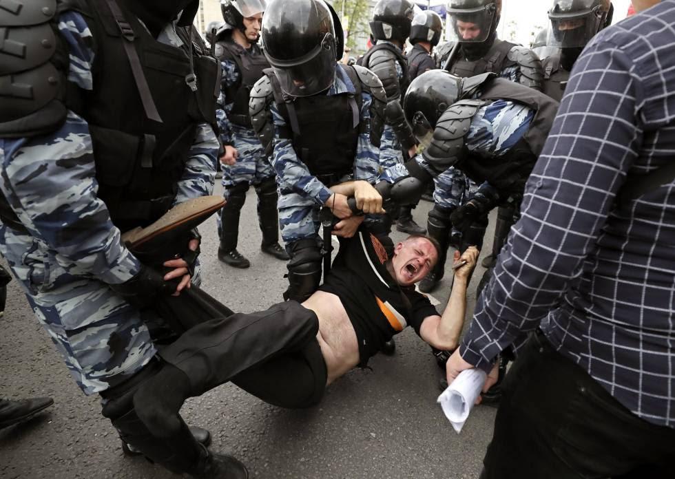 Miembros de la policía detienen a uno de los participantes de la manifestación opositora en Moscú.