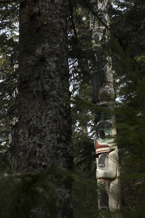 figures of the Spencer Pole, seen through trees, Totems Historic District, Kasaan, Alaska