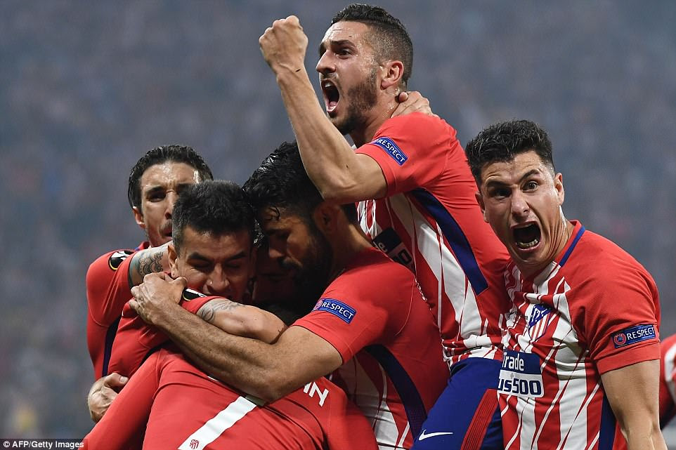 Griezmann is surrounded by his ecstatic Atletico team-mates as they take the lead over Marseille in Wednesday's final