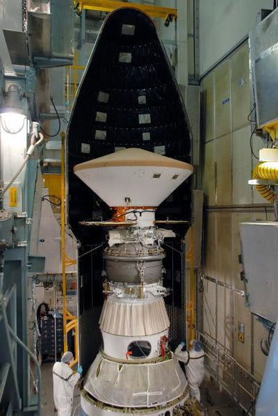 Technicians install a nose cone fairing around the Phoenix spacecraft after it is attached to its Delta II launch vehicle...in Pad 17-A at Cape Canaveral Air Force Station in Florida.
