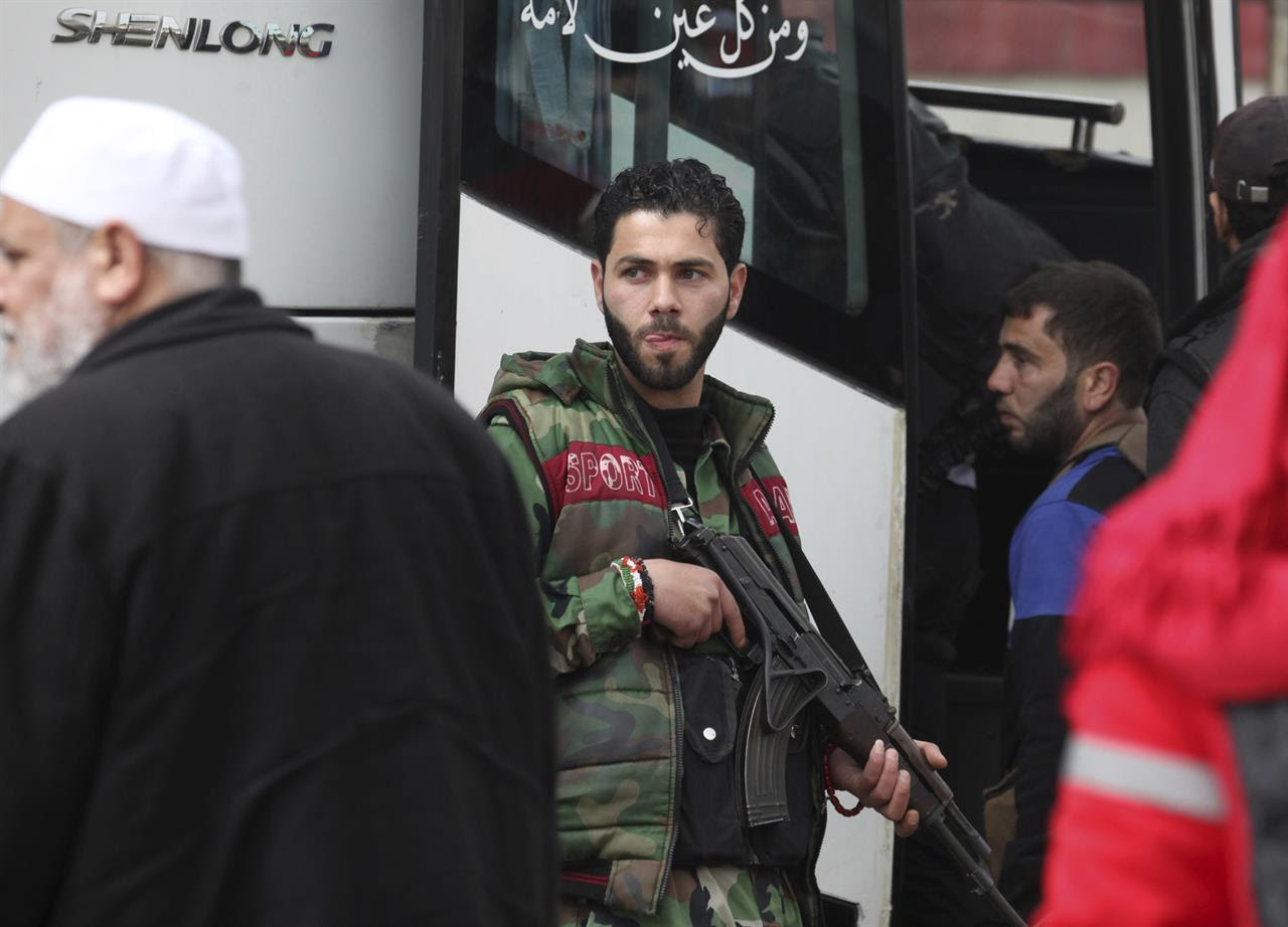Gunmen carrying their weapons leave the al-Waer neighborhood bound for a town on the Turkish border, in Homs, Syria, Saturday, March 18, 2017. Scores of Syrian opposition fighters and their families have begun leaving al-Waer, the last rebel-held neighborhood in the central city of Homs as part of a Russian-backed evacuation deal signed earlier this week. The city was once known as the epicenter of the 2011 uprising against President Bashar Assad.