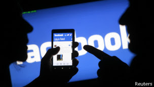 Siluetas de dos hombres frente al logo de Facebook