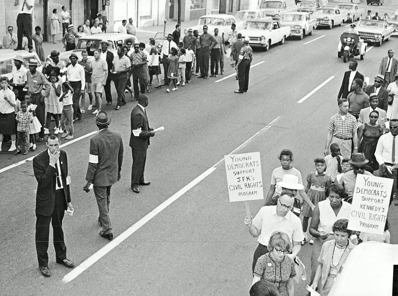 Description of  JUL 28 1963 - Marchers Move through Denver in Demonstration backing civil rights programs in Congress. Wayne Knox, head of the Denver Young Democrats and carrying the group's sign, was among some 1,000 marchers. (Duane Howell/The Denver Post)