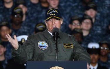 President Donald Trump wears a flight jacket and an admiral's cap aboard the Gerald R. Ford carrier