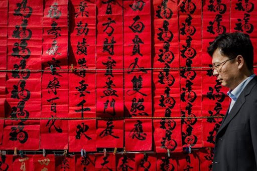 A man walks past New Year's calligraphy in Hong Kong on February 5, 2013