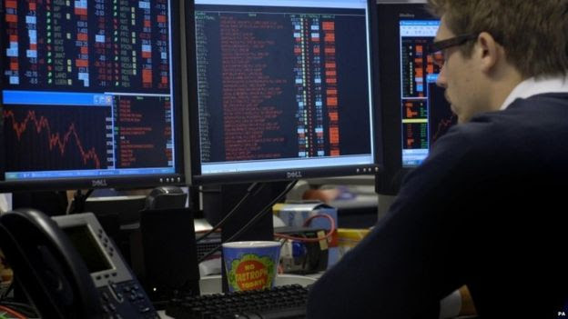 Trader in the City of London watches FTSE 100 index