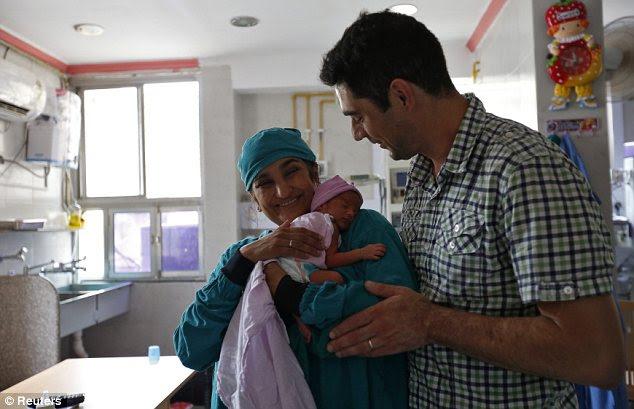 Proud: Rekha Patel, 42, holds her week-old-baby girl Gabriella, as her husband Daniele Fabbricatore, 39, looks on