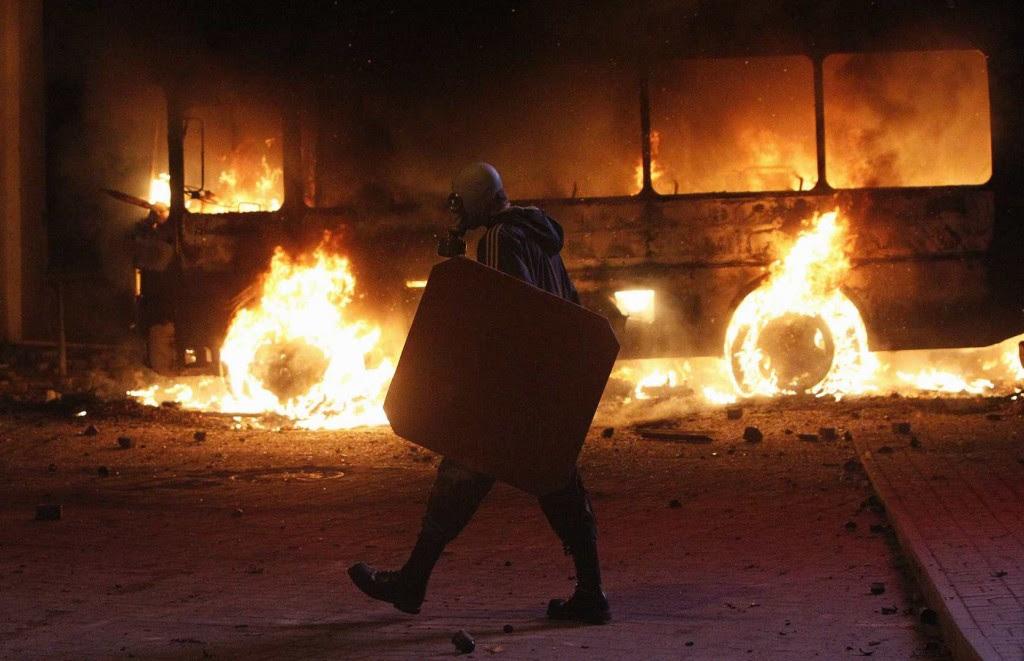 Учасник протесту на Грушевського на фоні згорілого автобусу, 19 січня 2013 року /Гліб Гаранич, Reuters/