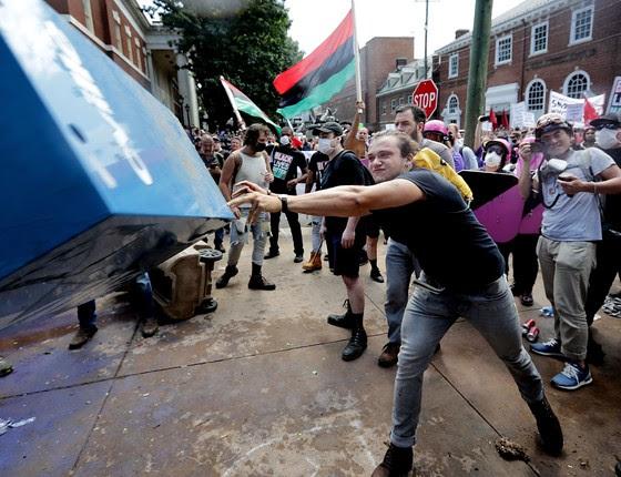 Manifestante antirrascismo atira caixa de jornais contra supremacistas brancos, em Charlottesville, na Virgínia (EUA) (Foto: Chip Somodevilla/Getty Images North America/AFP)