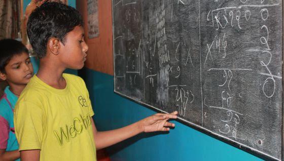 Los niños del Drop In center en Surat en clase de matemáticas repasan sus ejercicios.