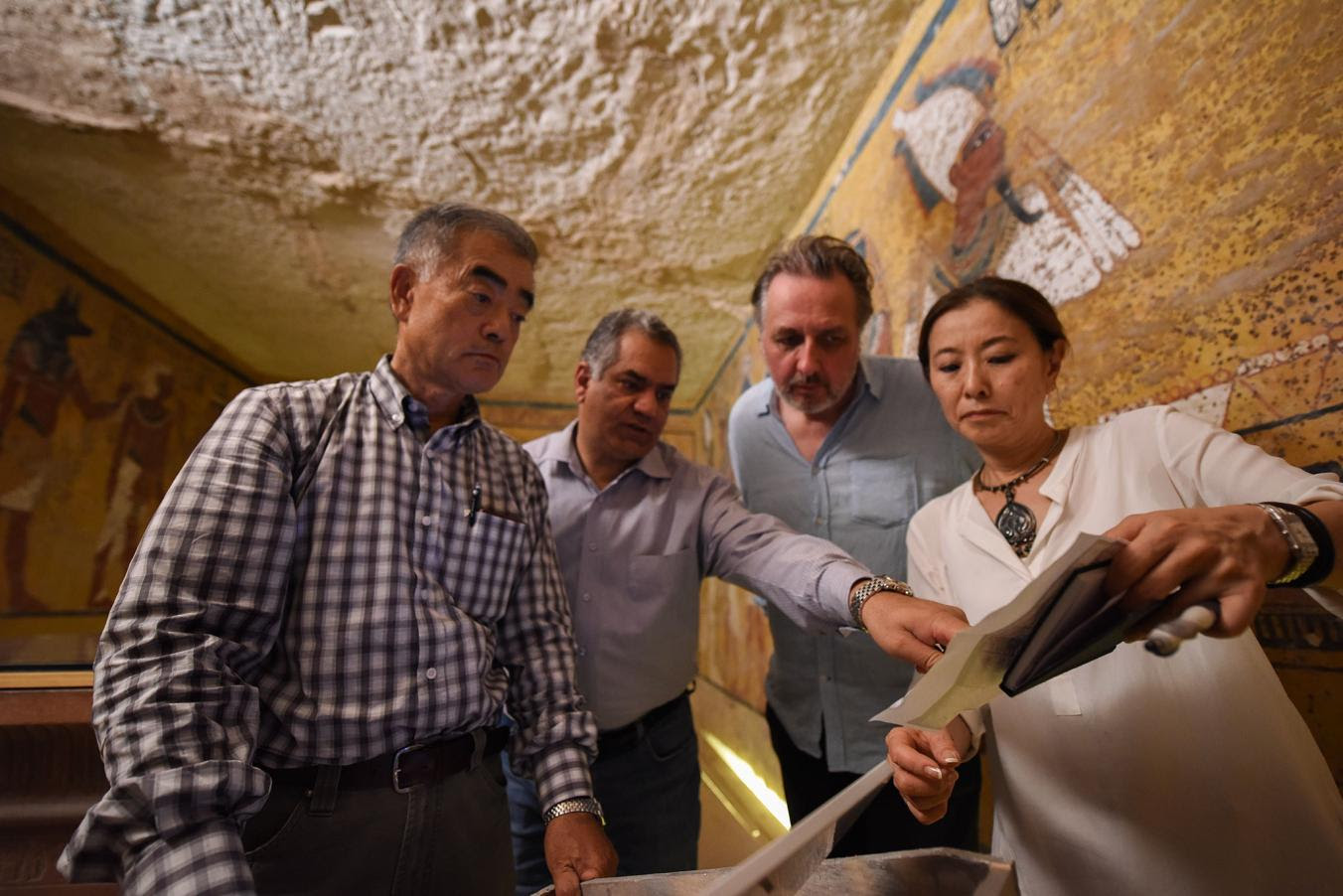 Hirokatsu Watanabe, Mamdouh Eldamaty, the Egyptian antiquities minister, and archaeologists Nicholas Reeves and Yumiko Ueno study an image of a painted wall scene. PHOTO: Brando Quilici, National Geographic
