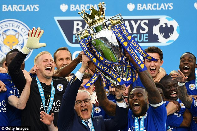 Wes Morgan (right) and Claudio Ranieri lift the trophy after Leicester clinched the Premier League title