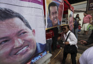 Pedestrians walk next to campaign posters of Venezuela's President Hugo Chavez in Caracas, Venezuela, Tuesday, Sept. 25, 2012. Chavez held a 10-point lead over rival Henrique Capriles in a polling company's final survey ahead of the Oct. 7 election, but the report released Tuesday showed Capriles narrowing the gap. (AP Photo/Fernando Llano)