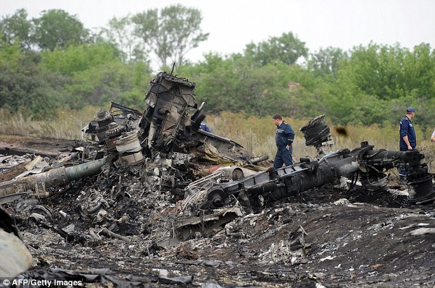 Rescuers stand on the site of the crash of the Malaysian airliner carrying 298 people, near the town of Shaktarsk, in rebel-held east Ukraine