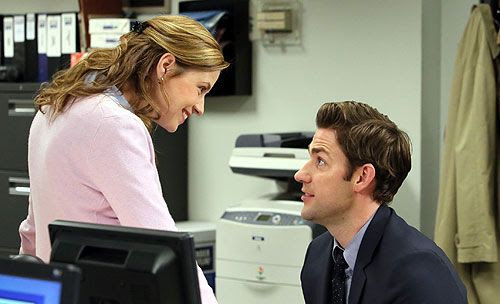 Pam Beasley hangs out at Jim Halpert's desk to chat with him in THE OFFICE.