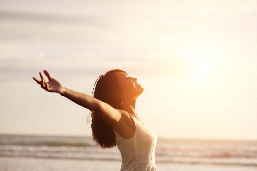 Mujer positiva abriendo los brazos para recibir al amanecer