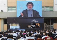 """Lebanon's Hezbollah leader Sayyed Hassan Nasrallah addresses his supporters via a screen, during a rally marking """"Quds (Jerusalem) Day"""",in the southern suburbs of Beirut, August 17, 2012. REUTERS/Sharif Karim"""