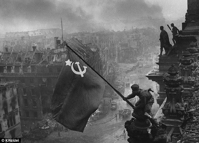 Terrible overwinning: Sovjet soldaten hijsen de rode hamer en sikkel vlag over Reichstag in Berlijn op 2 mei 1945 na uiteindelijk het verslaan van de nazi's