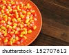 Candy corn in orange dish on rustic wood background with copy space. - stock photo