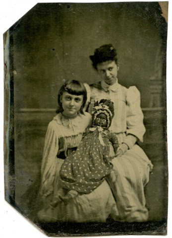 A tintype of a girl with a black doll and a woman, c1875.