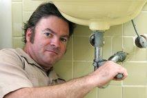 vodovodar popravlja sifon v kopalnici